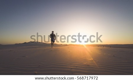 Back view silhouette of a runner man running along on the beach at sunset with sun in the background. Vintage effect style pictures.