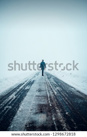 Back view silhouette of a young blonde girl walking in to nothing on a asphalt endless road. Winter foggy dark moody nature landscape. Harz Mountains National Park in Germany #1298672818