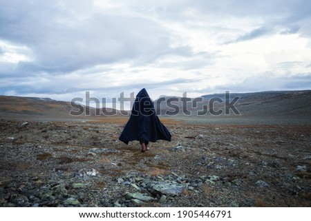 Back view silhouette of male traveler in medieval clothes. Man is walking through the mountains on the background of the dramatic cloudy sky.  Stock photo ©
