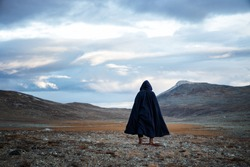 Back view silhouette of traveler man standing on the mountain.  A mysterious cloaked man. Medieval man in hooded cloak.