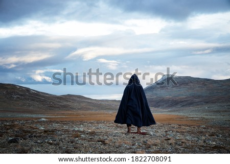 Back view silhouette of traveler man standing on the mountain.  A mysterious cloaked man. Medieval man in hooded cloak. Stock photo ©