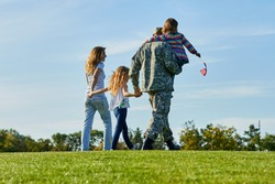 Back view soldier and his family are walking on the grass. Patriotic family with american flags, blue sky background.