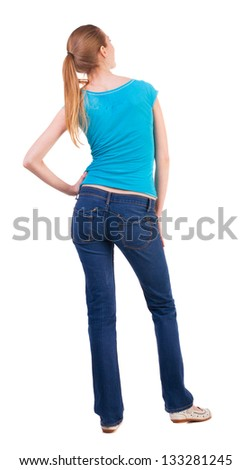 back view standing young beautiful  woman. girl  watching. Rear view people collection. backside view person.  Isolated over white. happy teenage girl looking to the side resting his hand on the hip