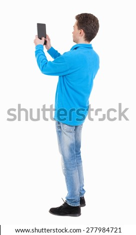 back view standing young man with tablet computer in the hands of. Rear view people collection.  backside view person.  Isolated over white background. guy in the blue sweater pictures of the tablet.