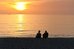Back view, very, far distance, of a senior couple, sitting on beach chairs, on a tropical shoreline, of sandy beach, watching a sunset, on the gulf of mexico