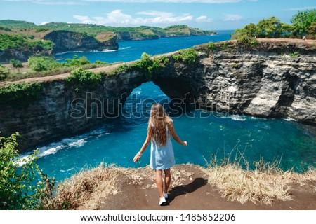 Back view woman on the edge of a cliff looking on broken beach. Broken Beach Nusa Penida - popular travel destination in Indonesia #1485852206