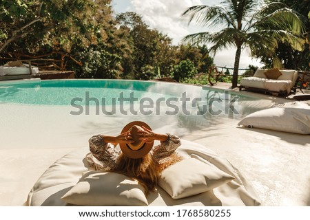 Back view woman wearing straw hat lie on sunbed  and enjoy sun tan near swimming pool with view on ocean and palm trees.  Relaxing summer day, Luxurious tropical vacation concept Photo stock ©