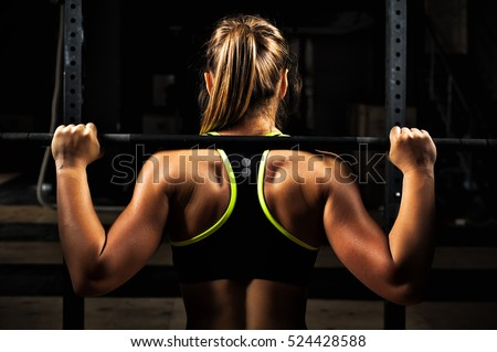 Stock Photo Back view young adult girl doing barbell squats in gym. Woman with muscular body doing lifting exercise.