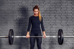 Back view young adult girl doing heavy duty squat in gym with barbell. Woman with perfect abs doing squat exercises. Blonde fit woman in great shape in Fitness