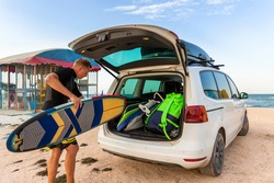 Back view young adult male surfer in wetsuit put out surf board kite equipment on sand beach from van vehicle with rooftop box ocean sea beach watersport spot camp.Adventure travel sport acitivity
