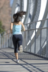 back view young beautiful and athletic sport woman running and jogging in urban training workout crossing modern metal city bridge in female runner body care and healthy lifestyle concept