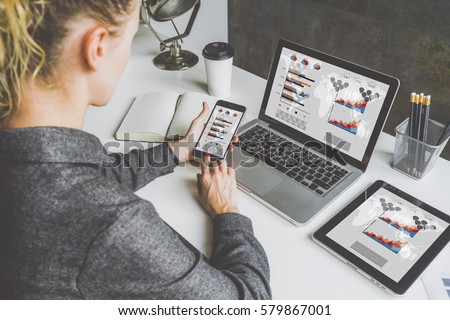 Back view. Young business woman sitting in office at table and using smartphone. On desk is laptop and tablet computer, on screen charts and graphs. Woman analyzing data. Student learning online.