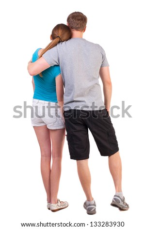 Back view young couple dressed for summer travel couple young people. beautiful friendly girl and guy together. Rear view. Isolated over white. Sports heterosexual couple hugging in summer shorts - stock photo