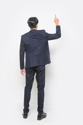 back view Young handsome man wearing black suit standing shirt  pointing forward serious over isolated white background