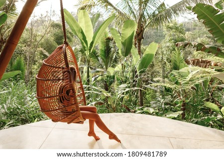 Back view yourist woman swing on wicker rattan hang chair in the jungle, nature view. Enjoy vacation on tropical Bali island
