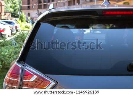 Back window of a car parked on the street in summer sunny day, rear view. Mock-up for sticker or decals #1146926189