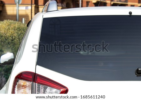 Back window of a white car parked on the street near houses, rear view. Mock-up for sticker or decals ストックフォト ©