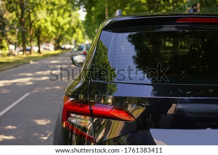 Back window of black car parked on the street in summer sunny day, rear view. Mock-up for sticker or decals ストックフォト ©
