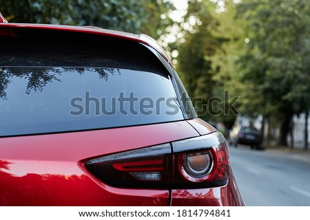 Back window of red car parked on the street in summer sunny day, rear view. Mock-up for sticker or decals Сток-фото ©