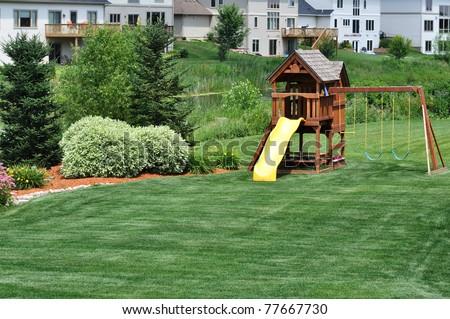 Back Yard Wooden Swing Set on Green Lawn