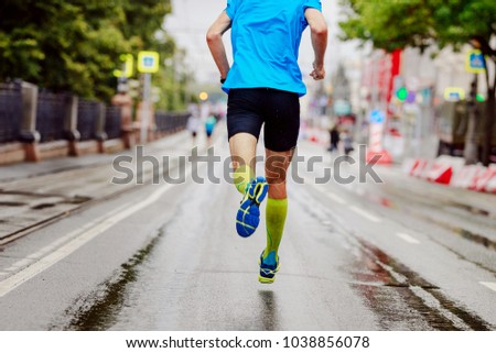back young runner in yellow compression socks running urban marathon #1038856078