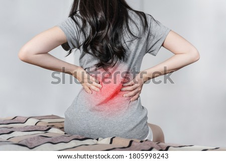 Backache and Lower back pain. Young woman suffering from back pain, on bed after waking up