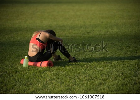 Backache, back pain, fatigue. Tired woman in sportswear relax after workout, training. Sportswoman sit on green grass with gym equipment on summer. Sport, training, workout. Health, bodycare, wellness #1061007518