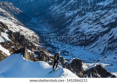 Backcountry skier athlete looking over steep cliff into the Bartolf Creek drainage below him. He stands near an unnamed peak after summiting, just above the Snowbird Glacier and Snowbird Hut. Stock fotó ©
