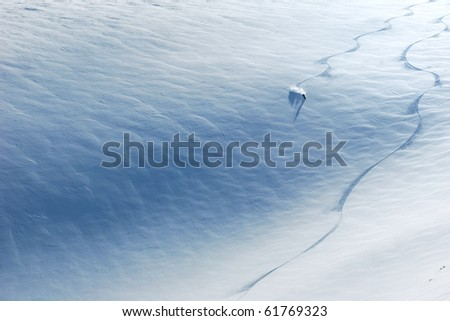 Backcountry skier riding down the huge snowfield splashing powder snow.