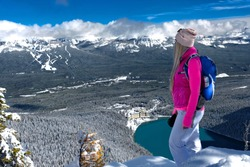 Backcountry skier woman standing on mountain top looking at view of ski runs and lake in winter.  Lake Louise Ski resort  in Banff National Park. Alberta. Canada
