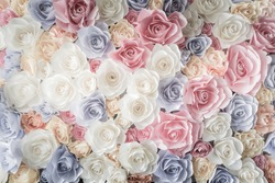 Backdrop of colorful paper roses background in a wedding reception with soft colors.