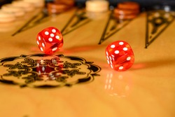 Backgammon board. Rolled red transparent dices over game board.