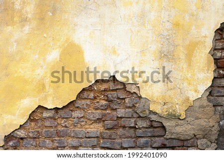 Background an old wall with crumbling plaster painted with an orange paint and exposed red bricks Foto stock ©