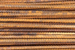 Background and rusty iron reinforcement rods. Red orange color of iron oxide on reinforcement bars