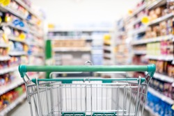 Background and wallpaper of shopping cart in supermarket departmentstore for choosing and buying grocery things at shelf. Time for shopping household goods, snacks, food, fruit, beverages and other.