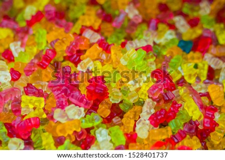Background - assortment of delicious marmalade jelly gummy bears for sale on counter of shop, grocery, market, cafe. Dessert, copy space, sweet food, pattern and confectionery concept
