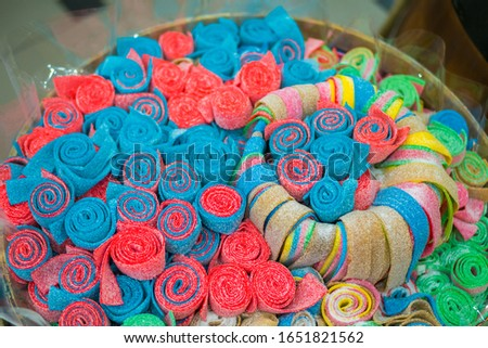 Background - assortment of delicious marmalade jelly roll candies for sale on counter of shop, grocery, market, cafe. Dessert, copy space, sweet food, pattern and confectionery concept