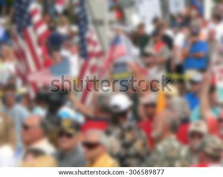 Background blur of crowd at political rally in the United States holding signs and carrying US flags. Great image for upcoming election cycle in 2016 presidential campaigns. Copy space
