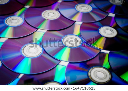 Background CD and DVD discs laid out on a flat surface. Background for saving information. Abstraction.
