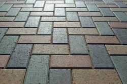 Background - colorful cobblestone pavement of the new paving stones. Diminishing perspective. Backlight.