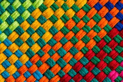 Background completely covered by diagonally angled rainbow colored interweaving threads of stitched fabric