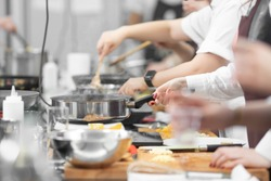 Background cook leads master class in cooking in kitchen.