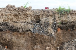 Background, cross-section, surface layer, rocky soil under the paved road, along the way, where the grass grows.