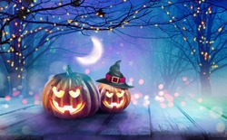 Background decoration for Halloween in blue purple tones. Two glowing pumpkins against evening sky with half moon in mystical forest. Magical atmosphere with festive illumination of lights on trees.