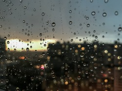 Background drops of water. Raindrop on window panes. Natural pattern of raindrops. Abstract shot of rain drops on glass. Night city and sunset outside window. Selective focus. Space for text or logo