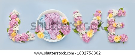 background for a photo shoot of a newborn baby in a flower lettering love of pink hydrangeas, yellow roses on a blue background