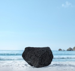 Background for cosmetic products on beach with sand. Natural volcanic rock stone podium. Empty showcase for packaging product presentation. Mock up pedestal in sunlight sea view.