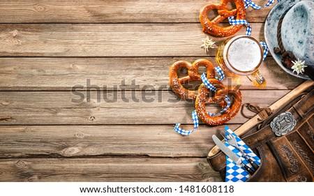 Background for Oktoberfest with Bavarian Lederhosen, hat, edelweiss, silverware, pretzels and beer stein on wooden tableHallo Photo stock ©