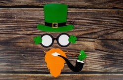 Background for St. Patrick's Day, March 17, Patrick's face in a leprechaun hat. Attributes of an Irish holiday. A copy of the text space.