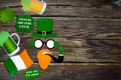 Background for St. Patrick's Day, March 17, with a festive garland, beer, leprechaun hat, clover on a wooden background. Attributes of an Irish holiday. A copy of the text space.